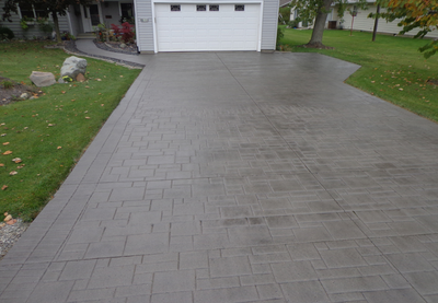 Stained and polished concrete driveway, stamped to look like pavers.