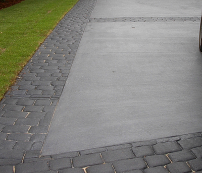 Gray textured driveway bordered by stamped concrete edging.