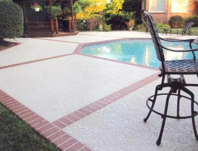 Concrete pool deck with decorative stamped brick design as the border.