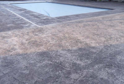 Gray stained pool deck around in ground pool.
