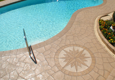 Decorative pool deck with compass design stamped into the concrete.