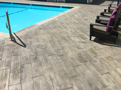 Wood grain plank design stamped into concrete pool deck.
