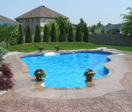 Concrete pool deck with plain concrete around the border and stamped concrete around that.