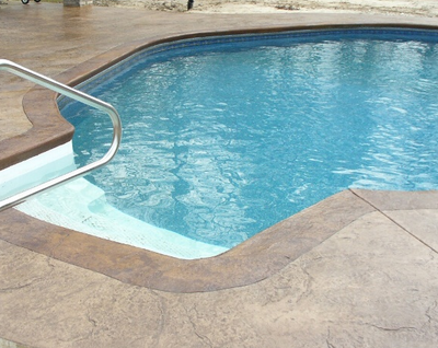 Indoor pool with a textured and stained concrete pool deck.