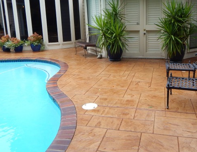 Pretty patio and pool deck made out of stamped concrete with two-tone border.