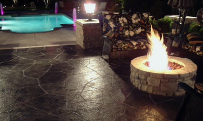 Textured pool deck next to a dark stained and stamped concrete patio and built in fire pit.